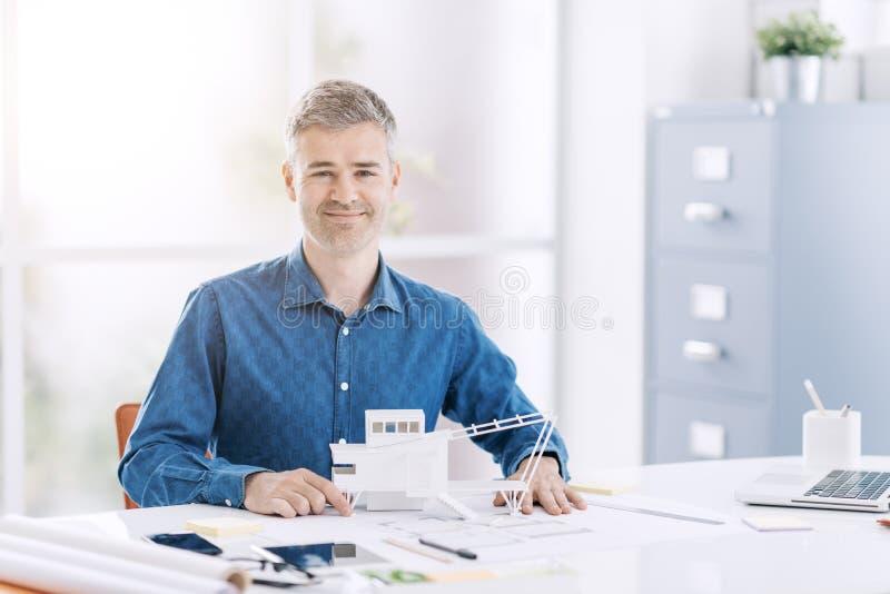 Профессиональный архитектор представляя в офисе с архитектурноакустической моделью современного здания стоковое изображение