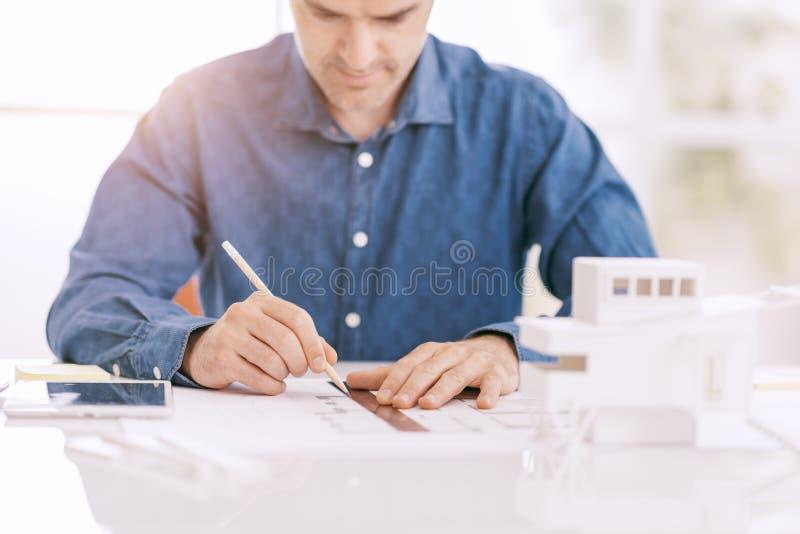 Профессиональный архитектор работая на столе офиса, он рисует с правителем на проекте проекта, архитектуре и проектирует концепци стоковые фото