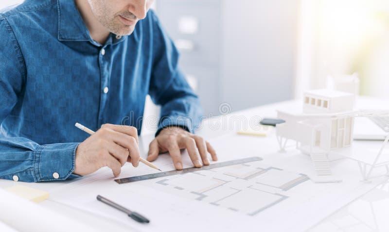 Профессиональный архитектор работая на столе офиса, он рисующ и делающ измерения на светокопии проекта, дизайн и стоковые фотографии rf
