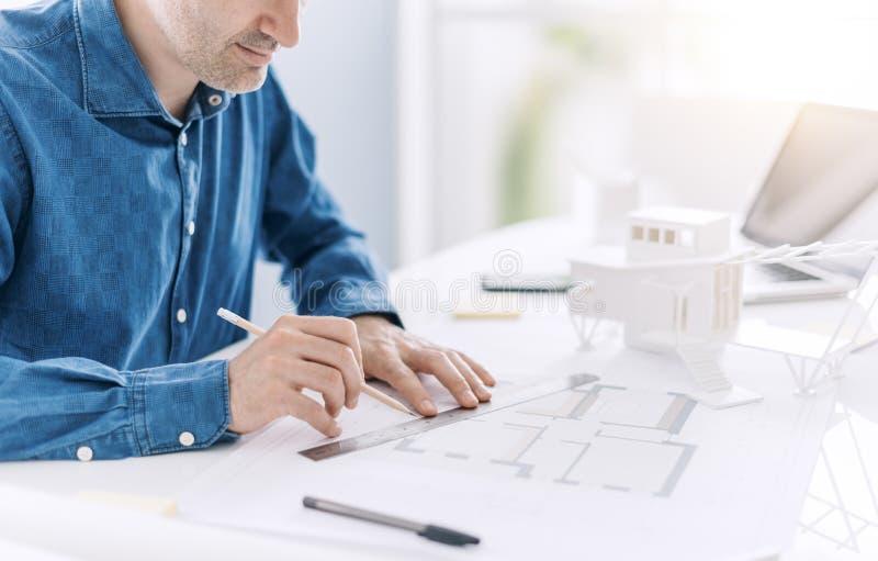 Профессиональный архитектор работая на столе офиса, он рисующ и делающ измерения на светокопии проекта, дизайн и стоковая фотография