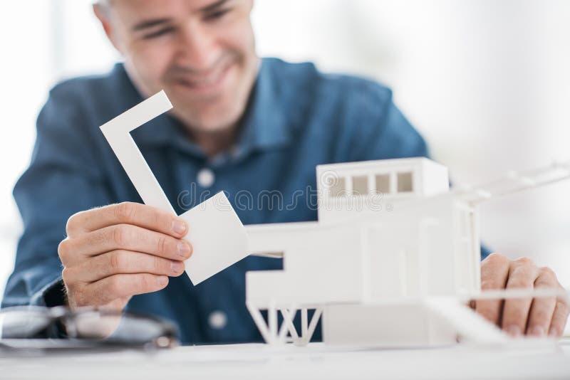 Профессиональный архитектор работая на столе офиса, он собирает архитектурноакустическую концепцию модели, дизайна и архитектуры стоковые изображения