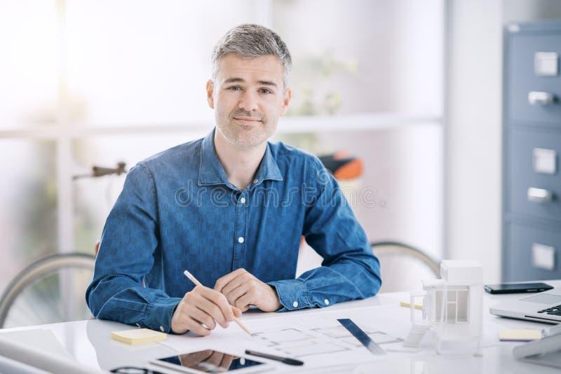 Профессиональный архитектор сидя на столе офиса и работая, он проверяет светокопию, инженерство и архитектуру проекта стоковое фото rf