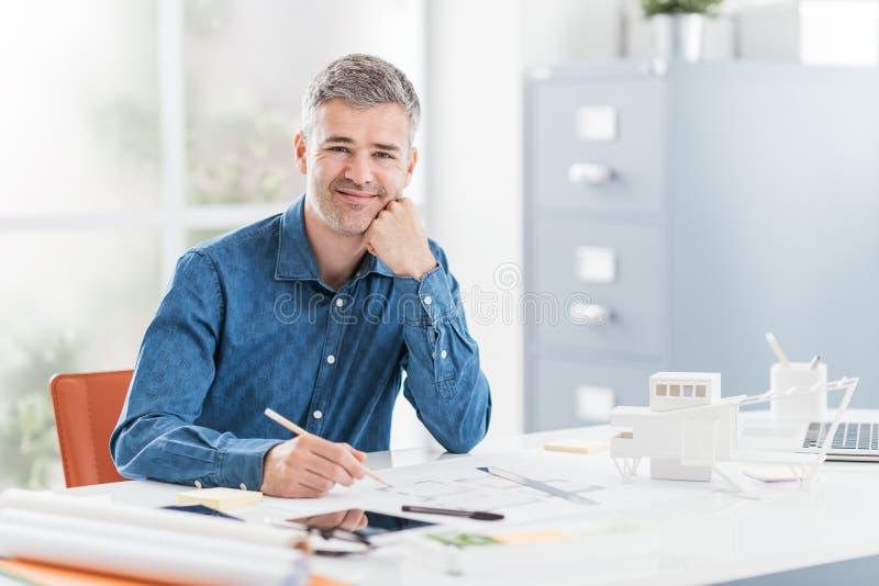 Профессиональный архитектор сидя на столе офиса и работая, он проверяет светокопию, инженерство и архитектуру проекта стоковая фотография rf