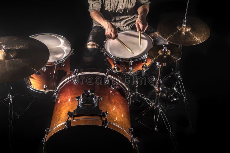 Профессиональный барабанщик играя на наборе барабанчика на этапе на черной предпосылке стоковая фотография
