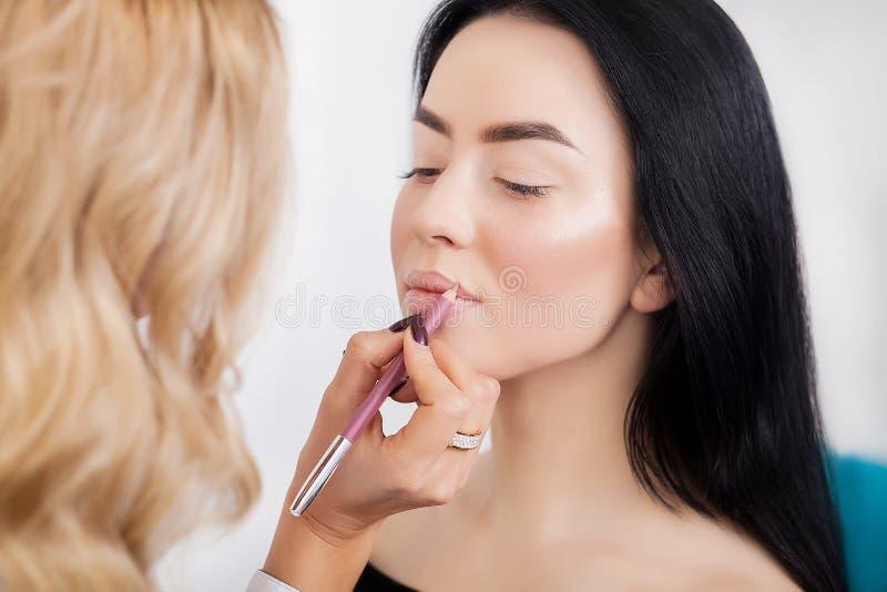 Профессиональный визажист прикладывая губную помаду стоковые фото