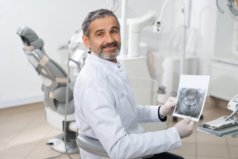 Профессиональный дантист представляя с зубоврачебным рентгеновским снимком в руках стоковая фотография rf