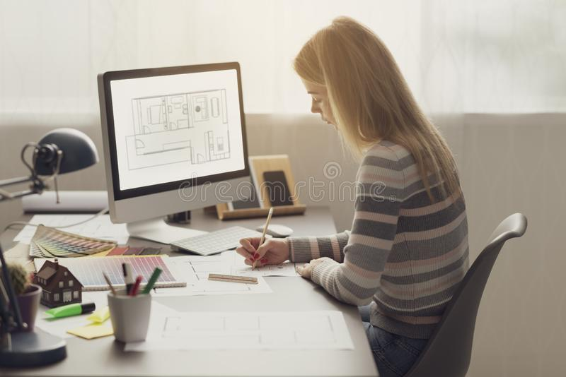 Профессиональный дизайнер по интерьеру работая в офисе стоковое фото