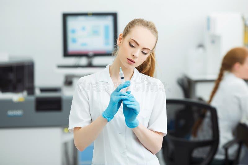 Профессиональный доктор с медицинским шприцем в руках, получая готовый для впрыски в современной лаборатории стоковое изображение