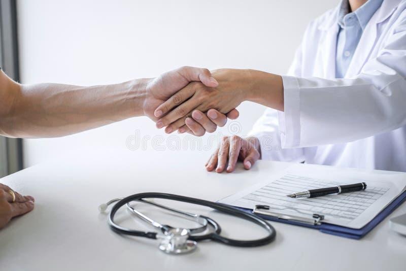 Профессиональный женский доктор в белом пальто тряся руку с пациентом после успешного рекомендует методы лечения после результато стоковое изображение