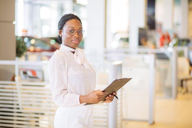 Профессиональный женский продавец работая в автосалоне стоковое изображение