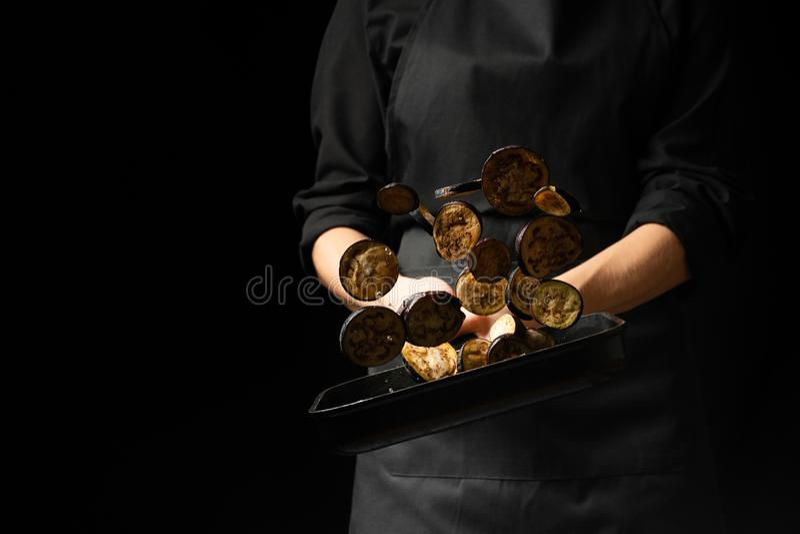 Профессиональный кашевар шеф-повар подготавливает блюдо с баклажанами в кастрюльке На черной предпосылке меню, книга рецепта, здо стоковое фото