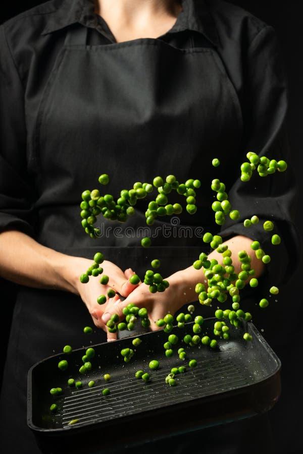 Профессиональный кашевар шеф-повар подготавливая блюдо с зелеными горохами в лотке На черной предпосылке меню, книга рецепта, здо стоковая фотография rf