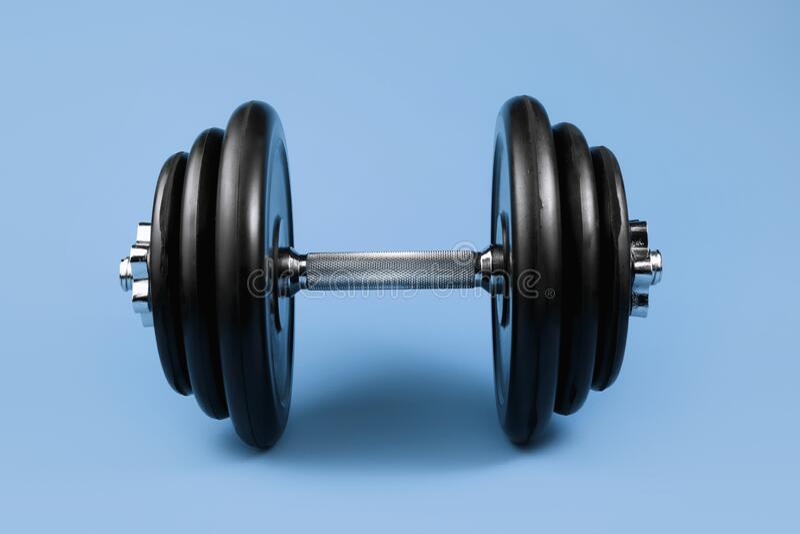 Профессиональный манкель и весовые пластины над голубым фоном Оборудование гимна Фитнес-концепция стоковая фотография rf