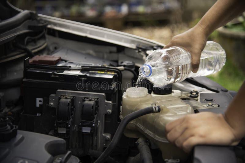 Профессиональный механик проверяя заполняя воду к радиатору автомобиля Co стоковые фото