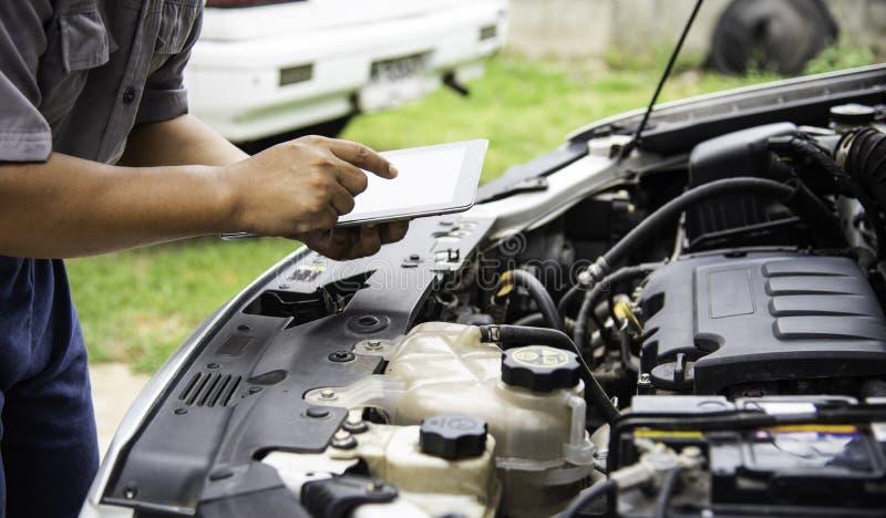Профессиональный механик проверяя поиск двигателя автомобиля для данных с t стоковое фото