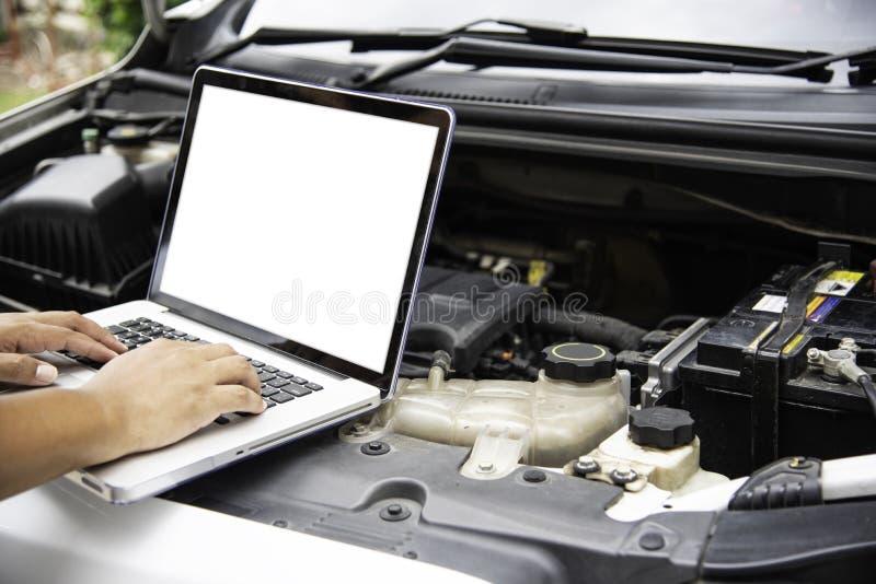 Профессиональный механик проверяя поиск двигателя автомобиля для данных с l стоковые фото