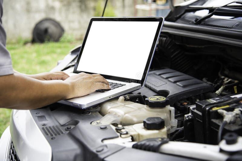 Профессиональный механик проверяя поиск двигателя автомобиля для данных с l стоковое фото
