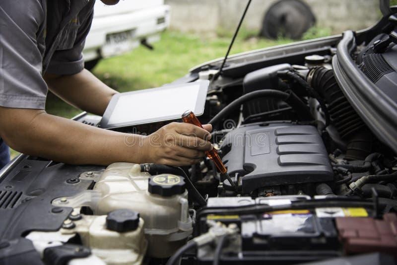 Профессиональный механик проверяя поиск двигателя автомобиля для данных с t стоковые фотографии rf