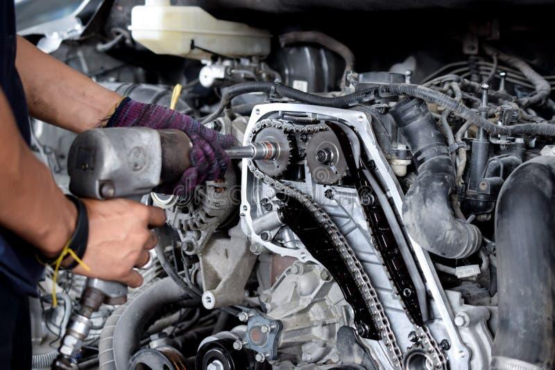 Профессиональный механик ремонтируя двигатель автомобиля стоковые фото