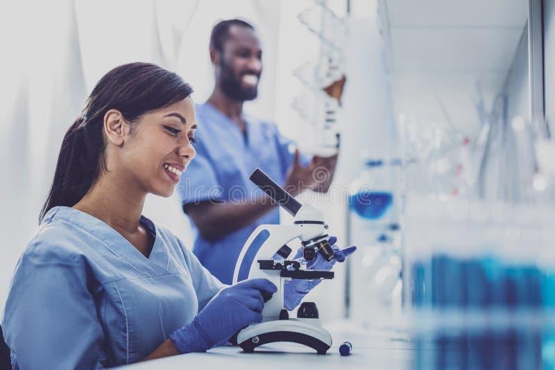 Профессиональный молодой химик используя микроскоп стоковая фотография