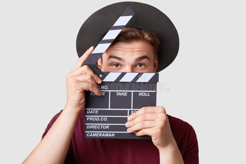 Профессиональный мужской актер готовый для снимая фильма, колотушки кино владениями, подготавливает для новой сцены, носит специа стоковое фото rf