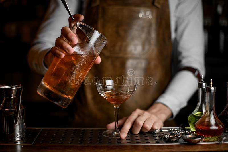 Профессиональный мужской бармен лить очень вкусный коричневый алкогольный напиток от измеряя чашки к стеклу коктейля стоковые фотографии rf