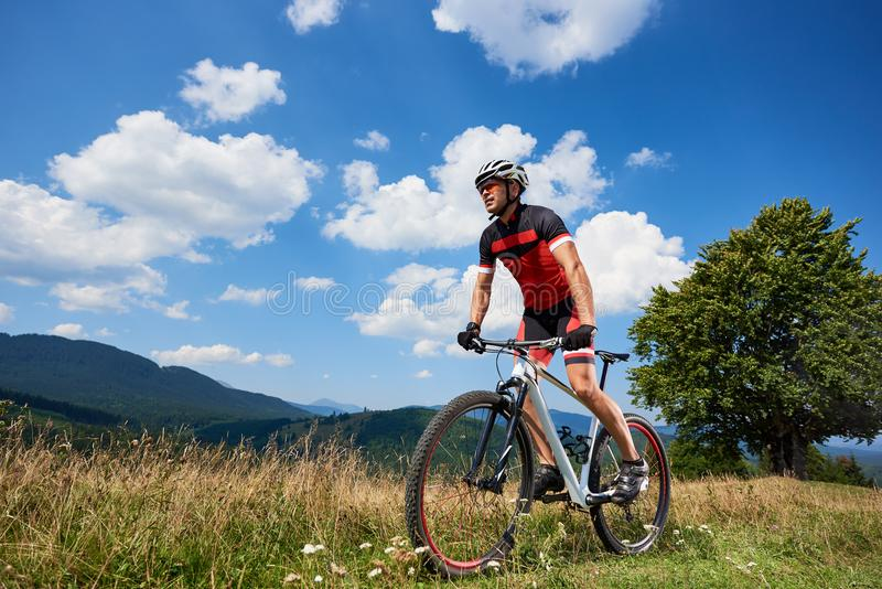 Профессиональный мужской велосипедист в sportswear и велосипеде шлема задействуя на следе стоковая фотография rf