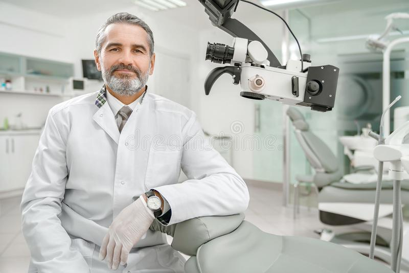 Профессиональный мужской дантист смотря камеру и усмехаться стоковое фото rf