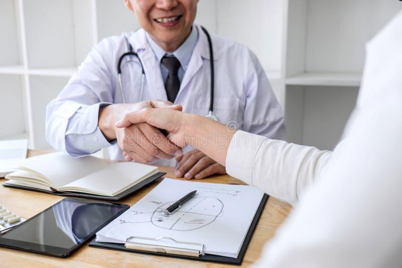 Профессиональный мужской доктор в белом пальто тряся руку с женским пациентом после успешного рекомендует методы лечения, медицин стоковая фотография rf