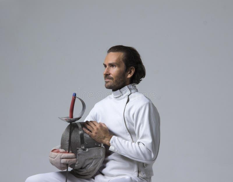 Профессиональный мужской фехтовальщик держа маску и саблю пока сидящ на стуле стоковые изображения