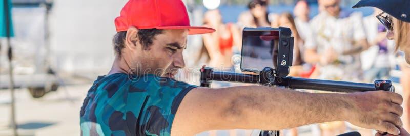 Профессиональный оператор steadicam использует систему стабилизатора камеры 3 осей на ЗНАМЕНИ набора освоенного производства, ДЛИ стоковое фото