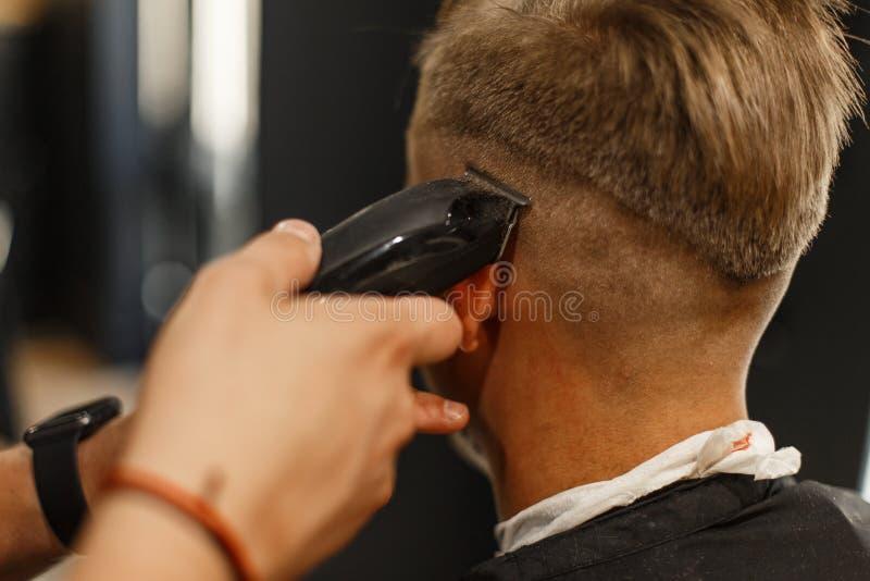 Профессиональный парикмахер делает hairdo ` s человека в студии стоковые изображения rf