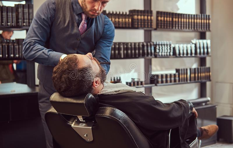 Профессиональный парикмахер моделируя бороду с ножницами и гребнем на парикмахерскае стоковое изображение