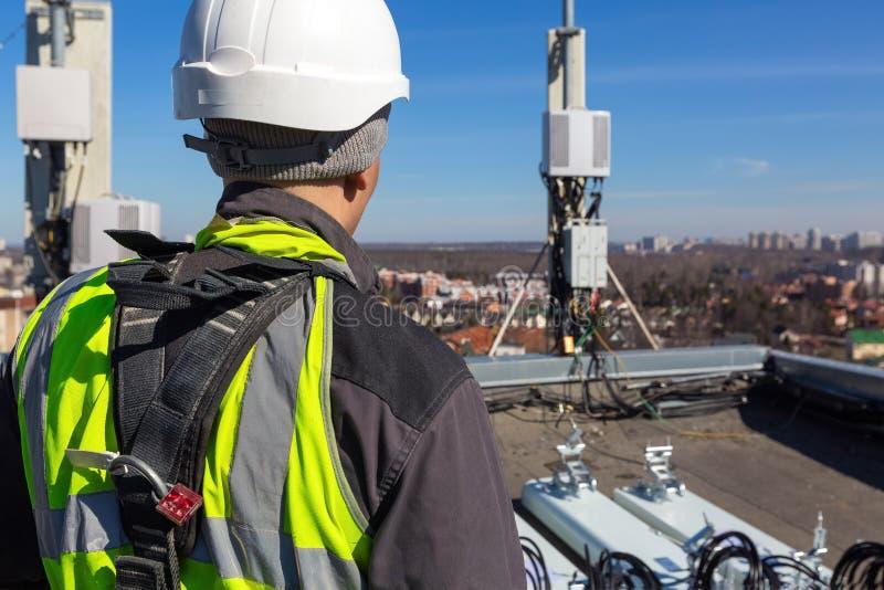 Профессиональный промышленный альпинист в шлеме и форме и антеннах диапазонов UMTS LTE DCS GSM, на открытом воздухе блоков радио  стоковые изображения