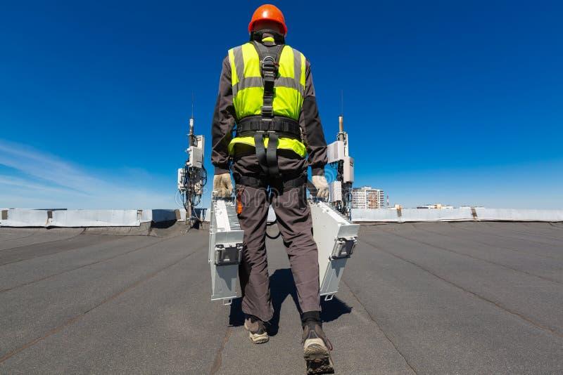 Профессиональный промышленный альпинист в шлеме и форме держит оборудование telecomunication в его руке и антеннах GSM стоковая фотография rf