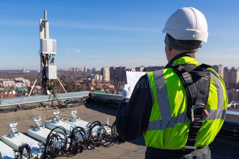 Профессиональный промышленный альпинист в шлеме и форме читает технические документацию и антенны UMTS LTE DCS GSM стоковая фотография