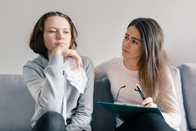 Профессиональный психолог ребенка разговаривая с девушкой подростка в офисе, плакать девушки стоковые изображения rf