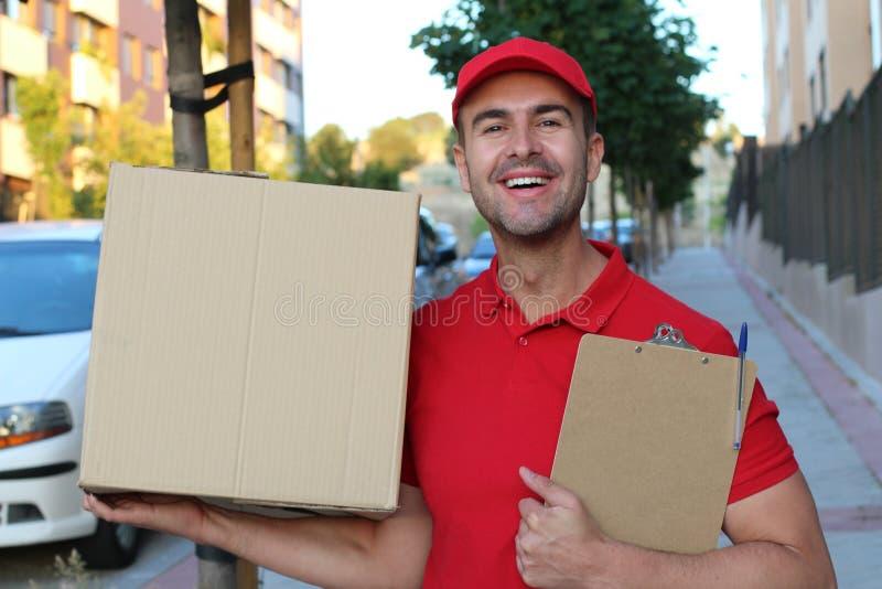 Профессиональный работник доставляющий покупки на дом усмехаясь на работе стоковая фотография