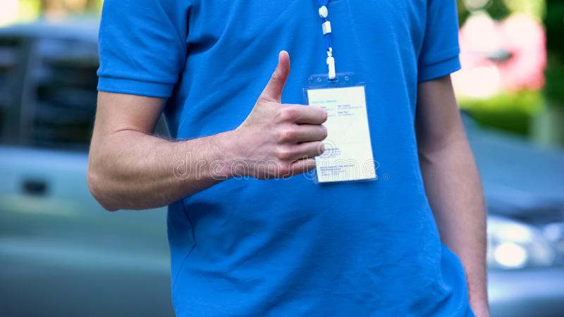 Профессиональный работник при значок показывая большие пальцы руки вверх, утверждение обслуживания компании стоковая фотография