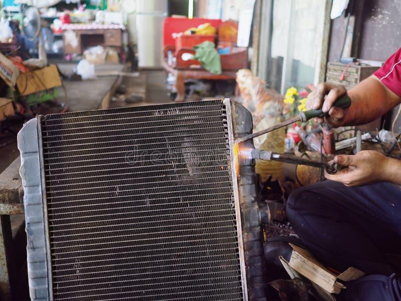 Профессиональный работник с охлаждать радиатора газа паяя автомобиля в мастерской гаража стоковые фотографии rf