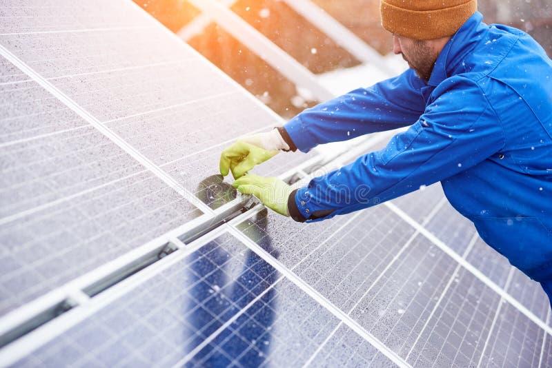 Профессиональный работник электрика устанавливая панели солнечных батарей стоковое фото rf