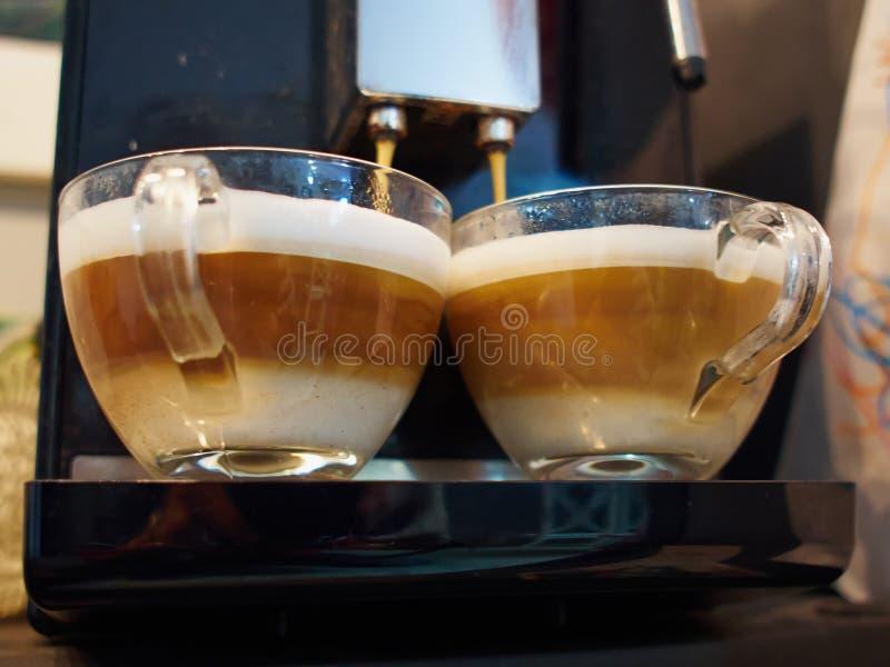 Профессиональный создатель машины кофе эспрессо лить свежий кофе стоковое фото