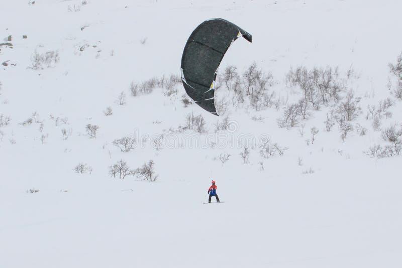 Профессиональный спортсмен всадника восхождения на борт змея со змеем в ездах неба в снеге на kiteboard Рекреационная деятельност стоковое фото