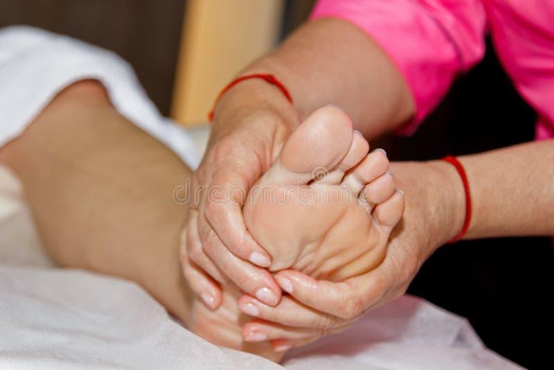 Профессиональный терапевтический массаж ноги Доктор женщины массажирует спортсмена в массажном кабинете тело и здравоохранение сп стоковое фото