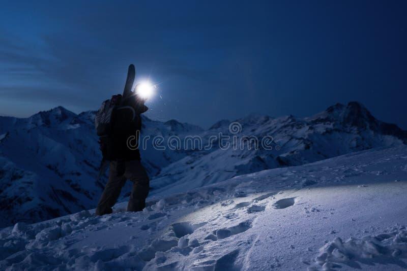Профессиональный турист совершает подъем на большой снежной горе на ноче Нося носка рюкзака, headlamp и лыжи Backcountry стоковые фото