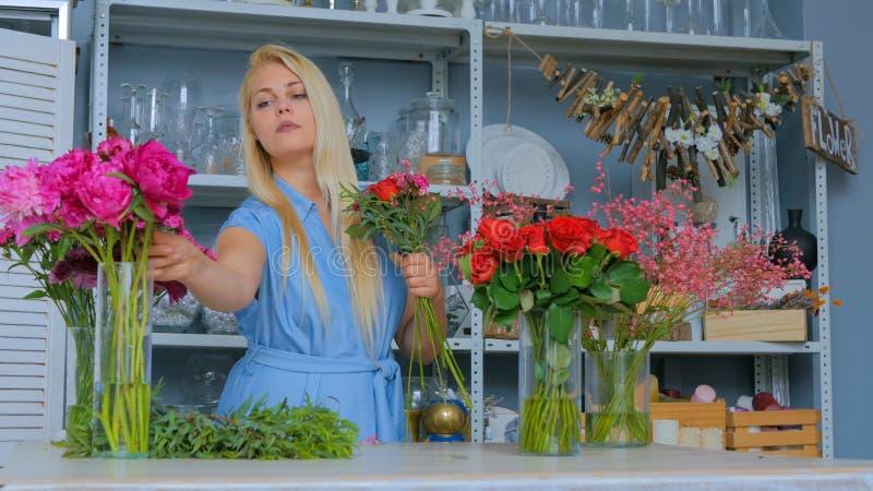 Профессиональный флорист делая флористический состав свадьбы на цветочном магазине стоковые изображения rf