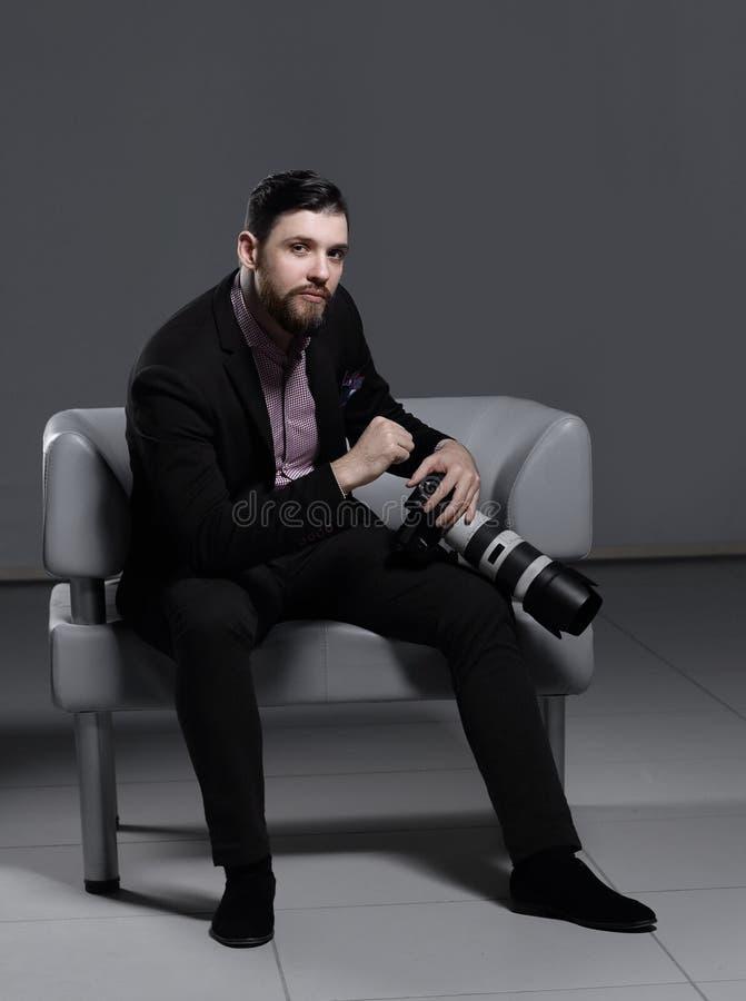 Профессиональный фотограф сидя на стуле офиса Изолировано на серой предпосылке стоковые изображения rf