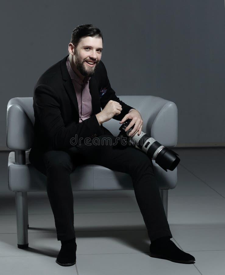 Профессиональный фотограф сидя на стуле офиса Изолировано на серой предпосылке стоковое изображение