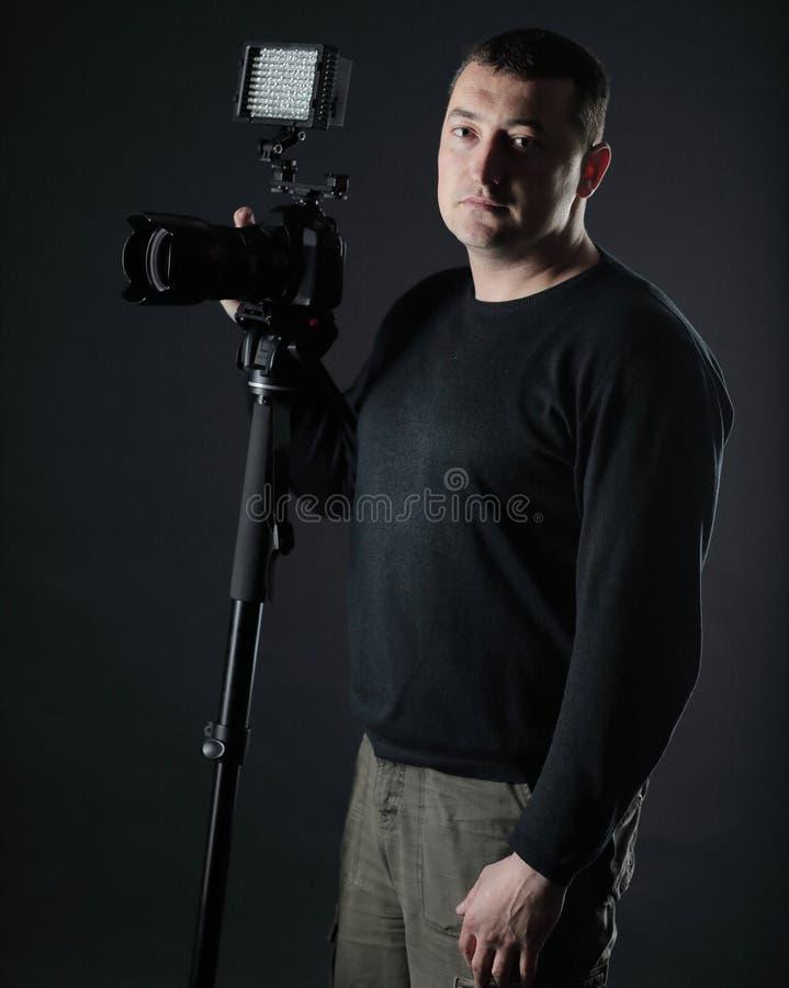 Профессиональный фотограф с камерой На черной предпосылке стоковые фото
