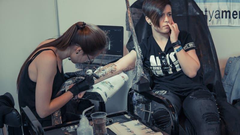 Профессиональный художник татуировки заполняет татуировку на теле людей стоковая фотография rf